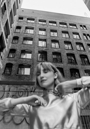 Low angle portrait of woman standing against building in city
