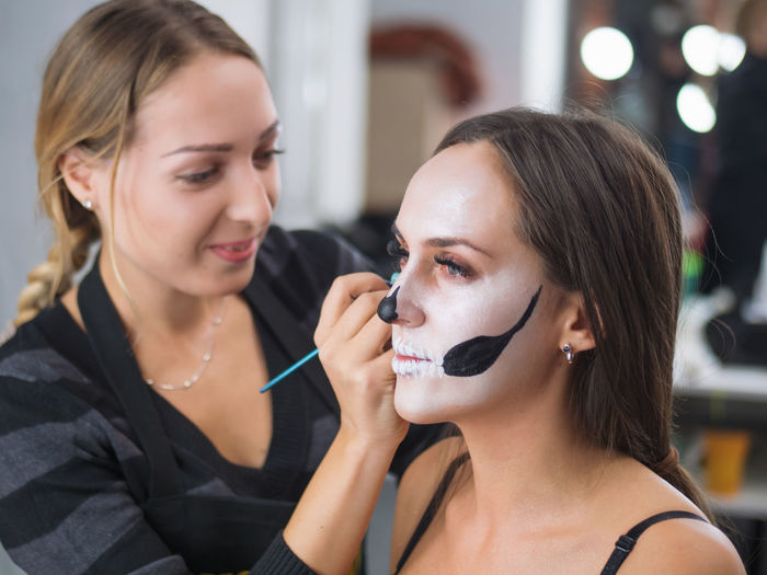Beautician Applying Make-Up To Young Woman