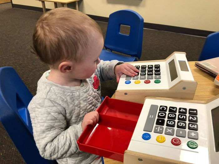 Baby girl playing with toy cash register on table