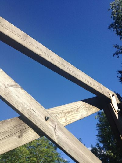 Close-Up Of Wooden Fence By Trees Against Blue Sky