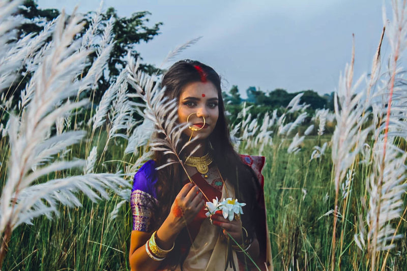Portrait of young woman wearing sari holding plant on land