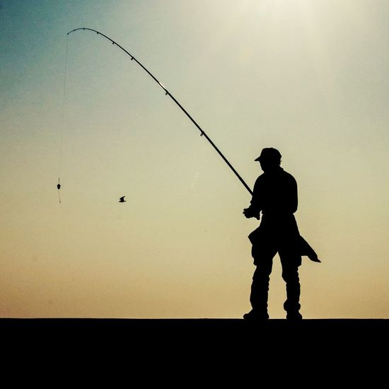 Silhouette of man fly fishing
