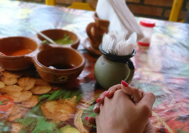 Cropped image of woman with hands clasped by bowls at table