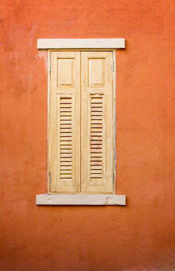 window on orange wall Architecture Brown Building Building Exterior Built Structure Close-up Closed Day Full Frame House No People Orange Color Ornate Outdoors Pattern Protection Security Shutter Wall - Building Feature Window Window Frame Wood - Material