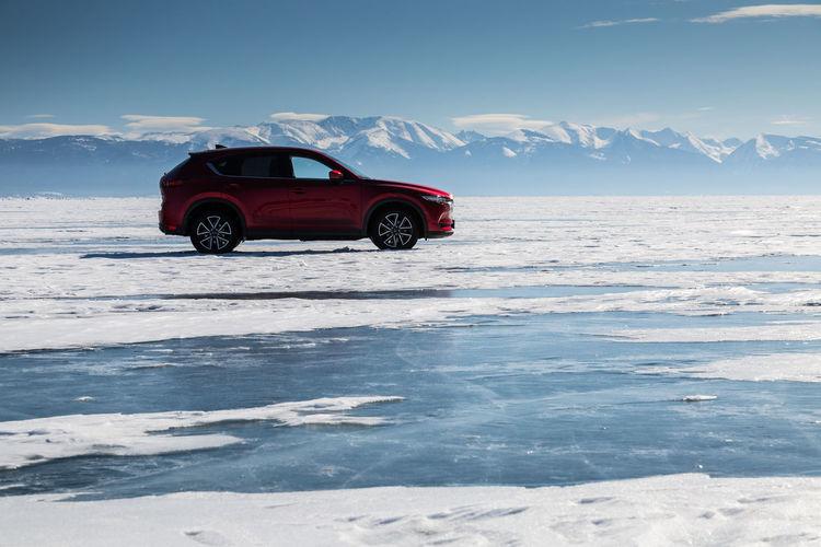 Car on snow covered sea against sky