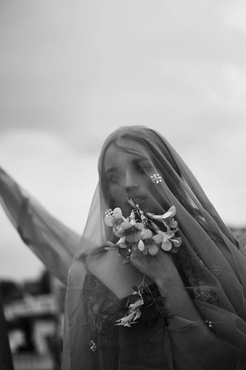 Midsection of woman holding flower standing against sky