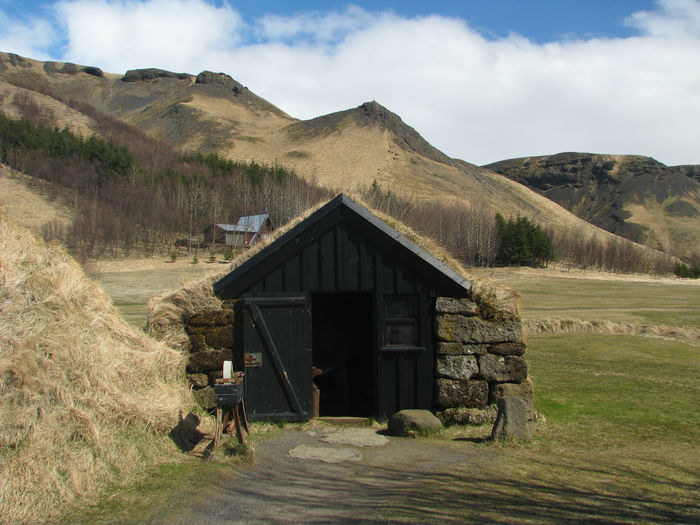 Icelandic cottage in a grassy field with mountains in the background