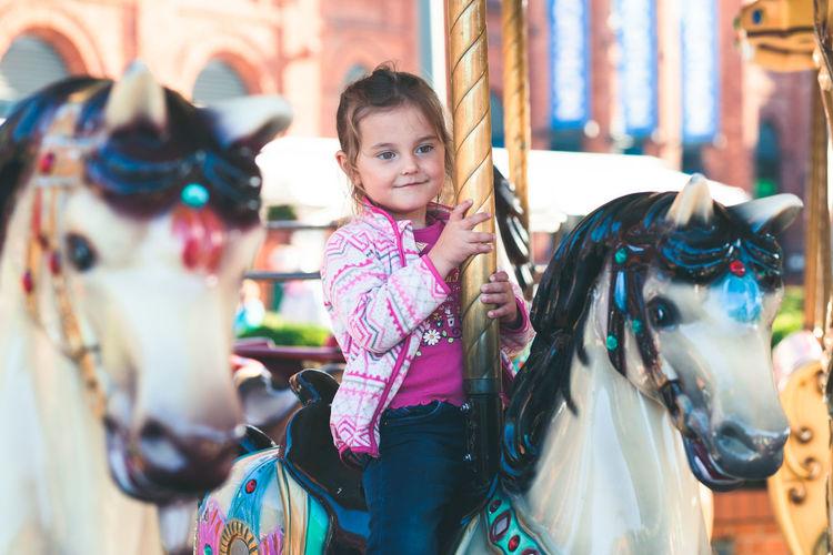 Cute girl sitting on carousel