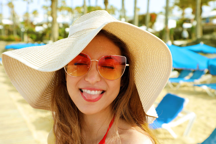 Close-Up Of Young Woman Wearing Hat And Sunglasses