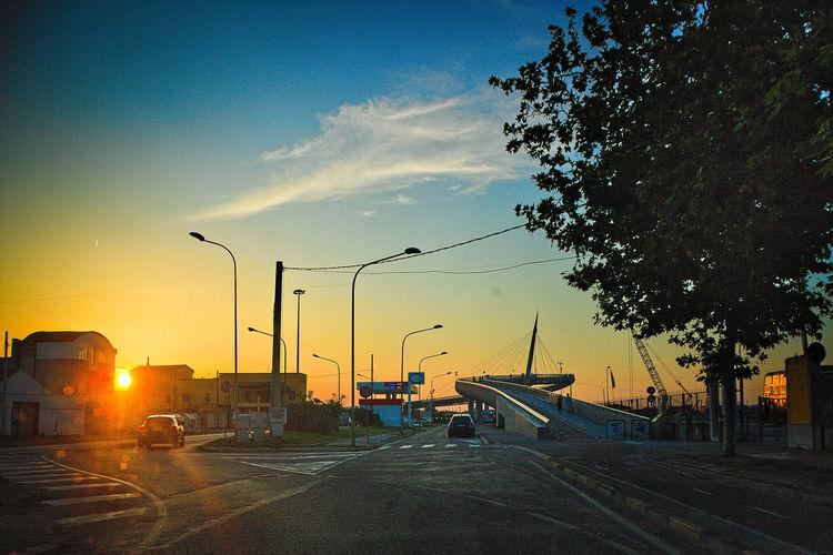 Cars on street against sky during sunset