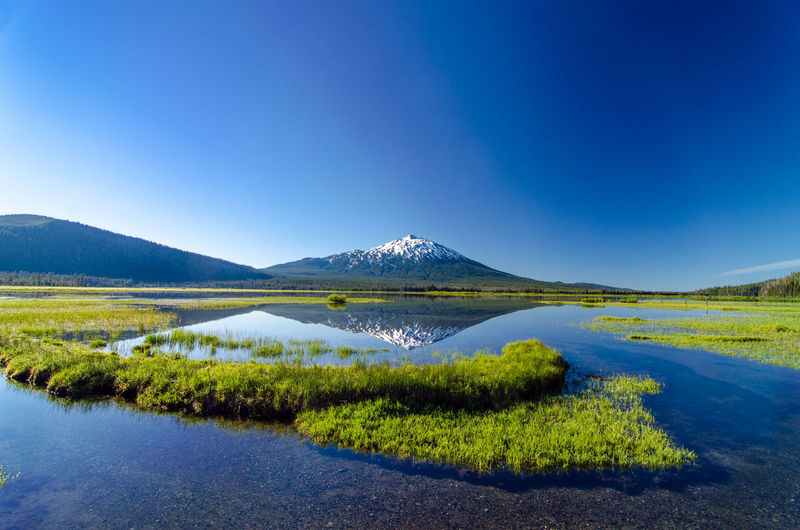 Scenic View Of Mt Bachelor And Sparks Lake Against Clear Blue Sky