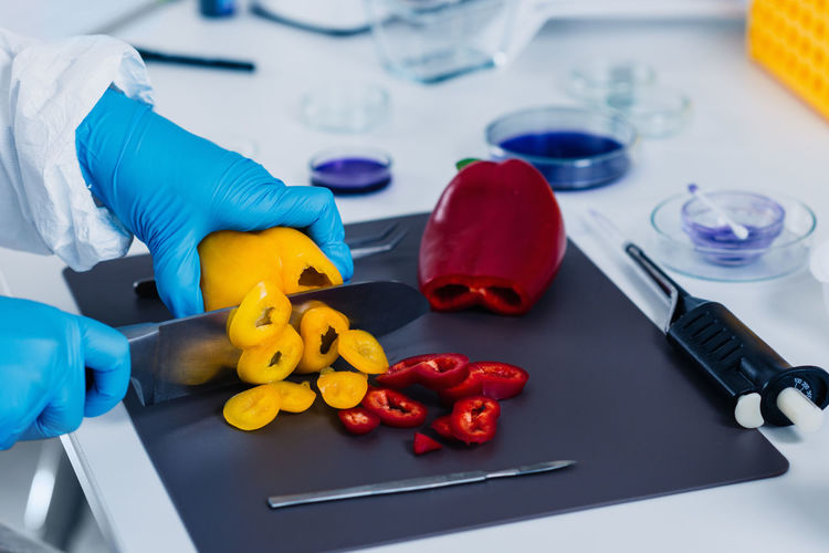 Cropped hands of scientist experimenting on bell peppers