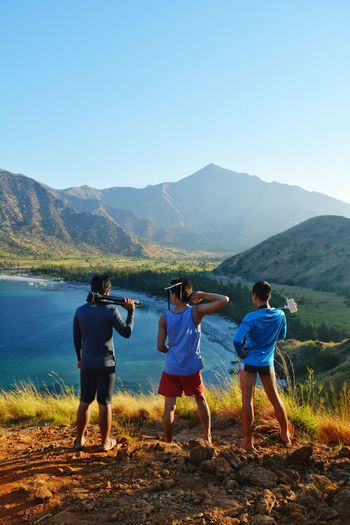 Rear View Of People Standing Holding Photographic Equipment By Lake