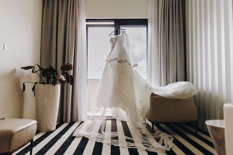 wedding dress hanging in hotel. Beautiful wedding dress with long veil. No People Indoors  Home Interior Wedding Dress Wedding Celebration White Color Window Hanging Day Event Domestic Room Curtain Life Events Textile Furniture Wedding Wedding Photography Hotel