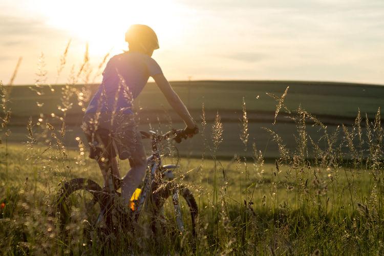 Evening biking in the sunset Evening Light Fahrrad MTB Sunlight Abendstimmung Bicycle Bike Biker Casual Clothing Evening Evening Sky Evening Sun Field Grass Growth Land Lifestyles Nature One Person Outdoors Real People Sport Sunlight Sunset Women