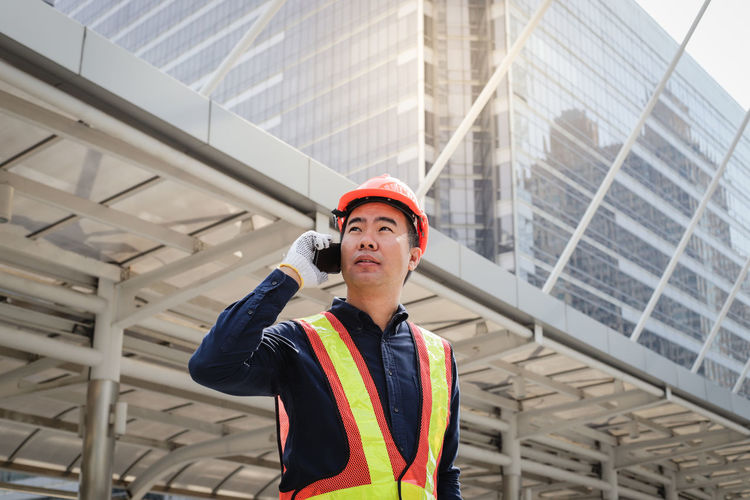 Architect talking on mobile phone while standing against buildings in city