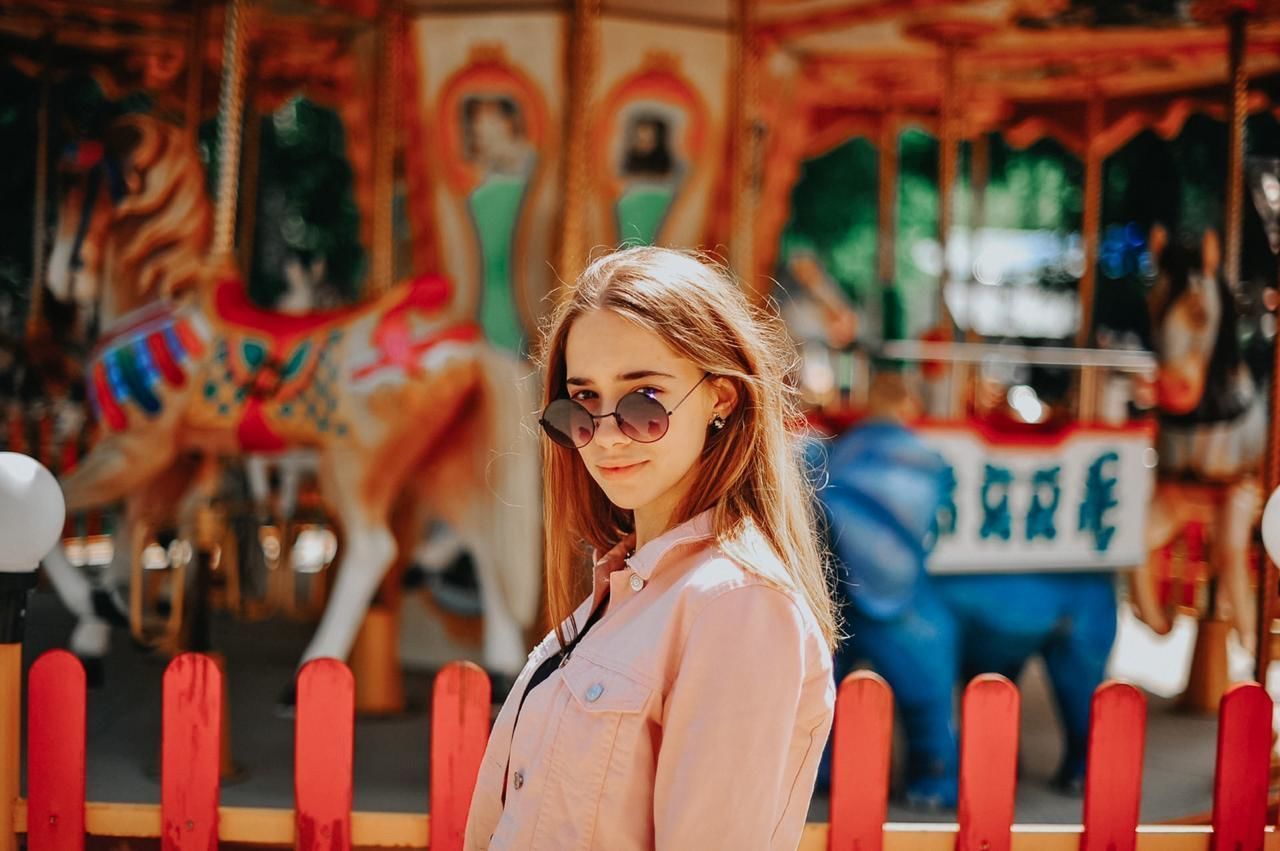 PORTRAIT OF YOUNG WOMAN WITH CAROUSEL IN AMUSEMENT PARK