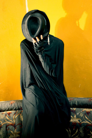Woman holding hat while standing against yellow wall