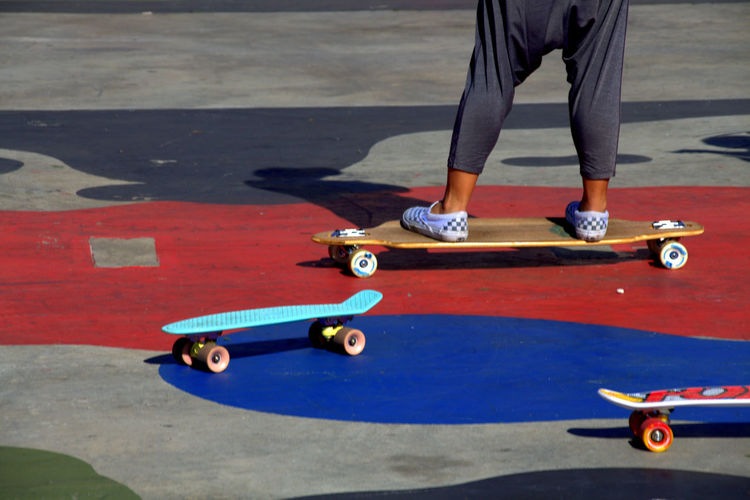 Low Section Of Child Skateboarding At Park