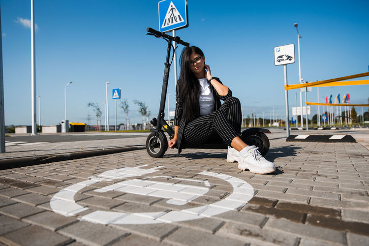 Portrait of woman with push scooter sitting on footpath against blue sky
