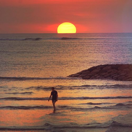Sunset man Sea Sunset Sky Water Beauty In Nature Horizon Land Real People Orange Color Tranquility Leisure Activity Tranquil Scene People Standing Sun Scenics - Nature Lifestyles Beach Horizon Over Water Nature