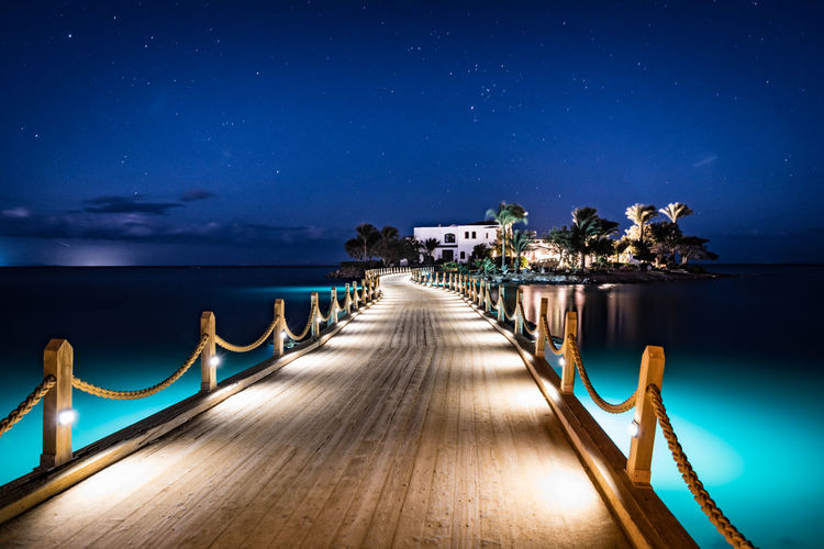 Sky Water Night Illuminated Sea The Way Forward Architecture Direction Blue Scenics - Nature No People Lighting Equipment Tropical Climate Built Structure Tranquility Horizon Over Water Outdoors Luxury Pier