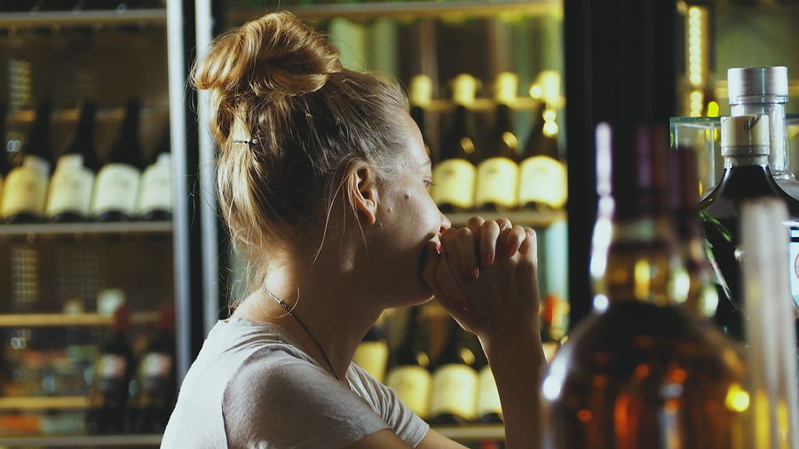 Young Woman With Hands Clasped At Bar Counter