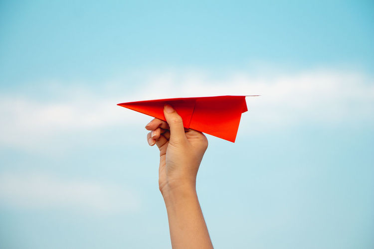 Cropped hand holding red paper plane against sky