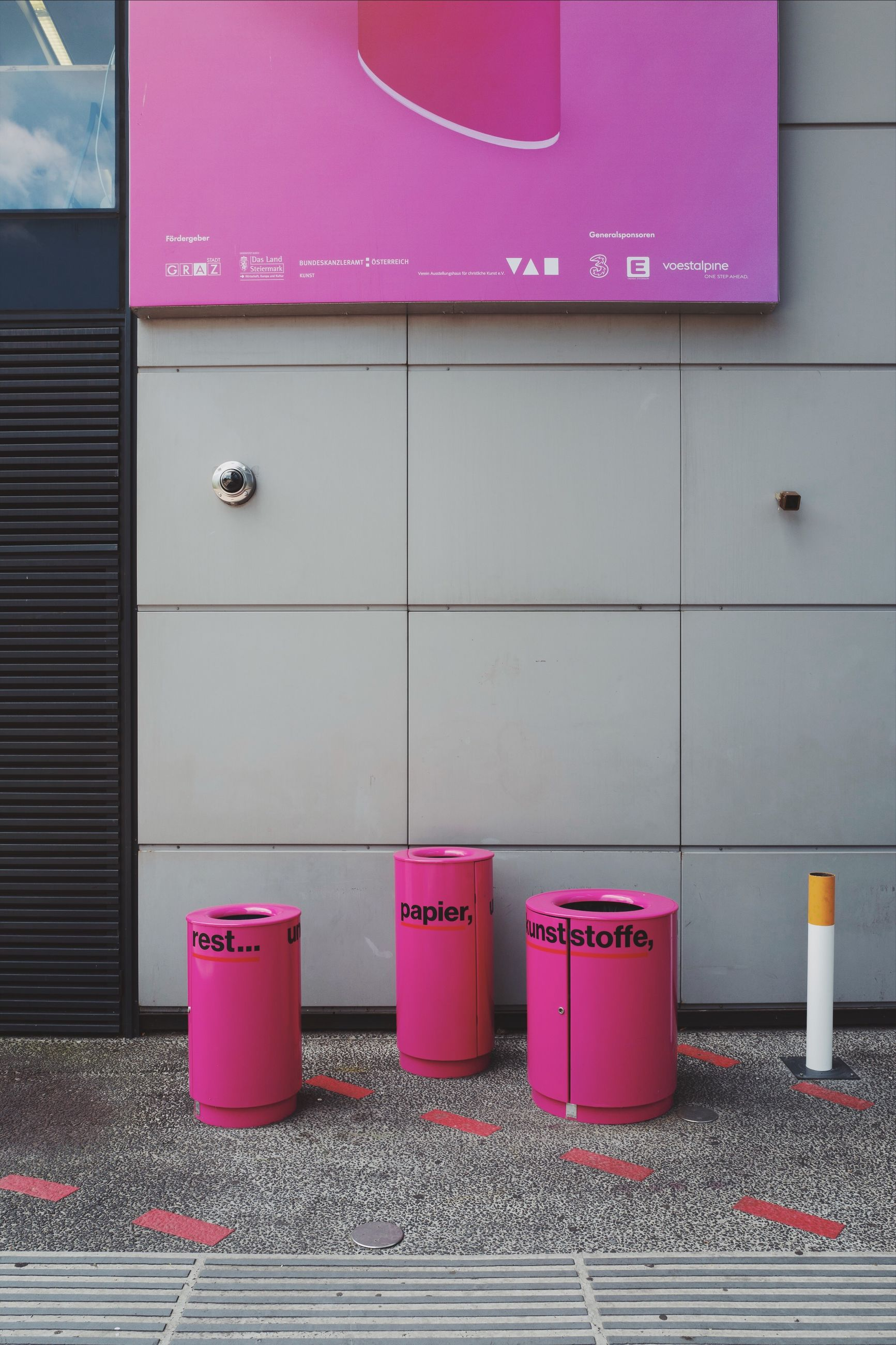 pink color, communication, text, no people, western script, garbage bin, container, day, architecture, non-western script, side by side, built structure, script, wall - building feature, indoors, sign, hygiene, red, number