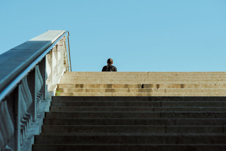 Low angle view of man on staircase against clear sky