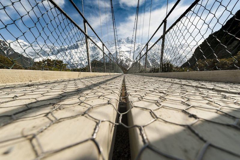 Surface level of chainlink fence against sky