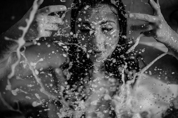 Woman splashing water on face