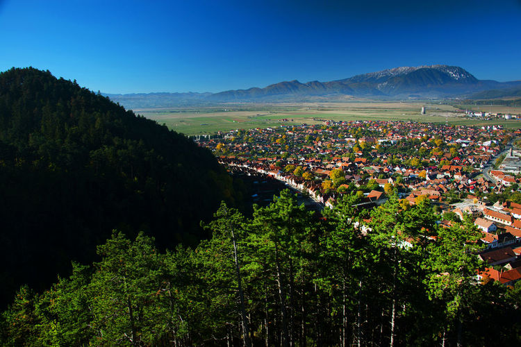 Scenic View Of Town By Mountains Against Blue Sky