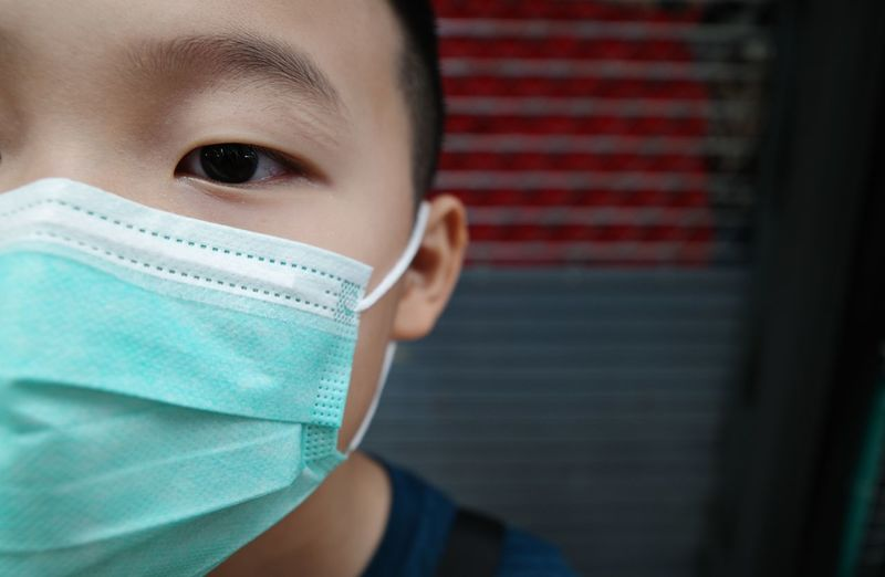 Close-up of boy wearing flu mask outdoors