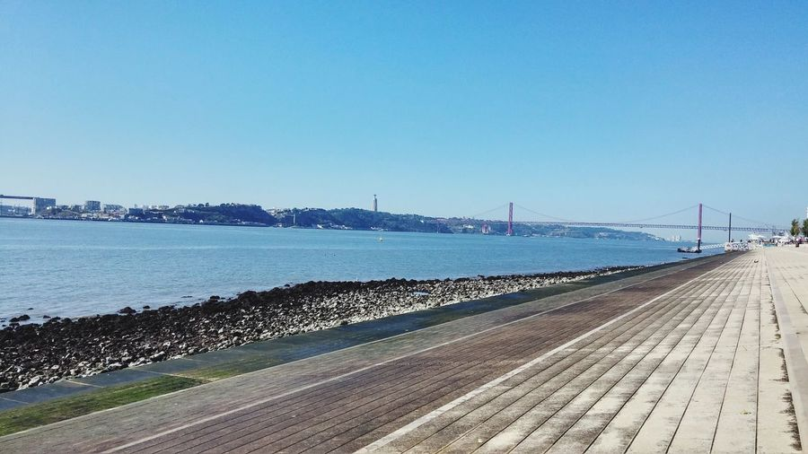 View of bridge over calm sea against clear sky
