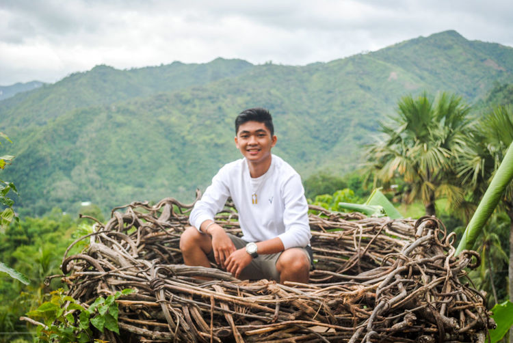 Portrait of smiling young man sitting on mountain nest