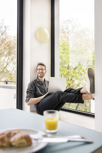 Mid adult man sitting by glass window