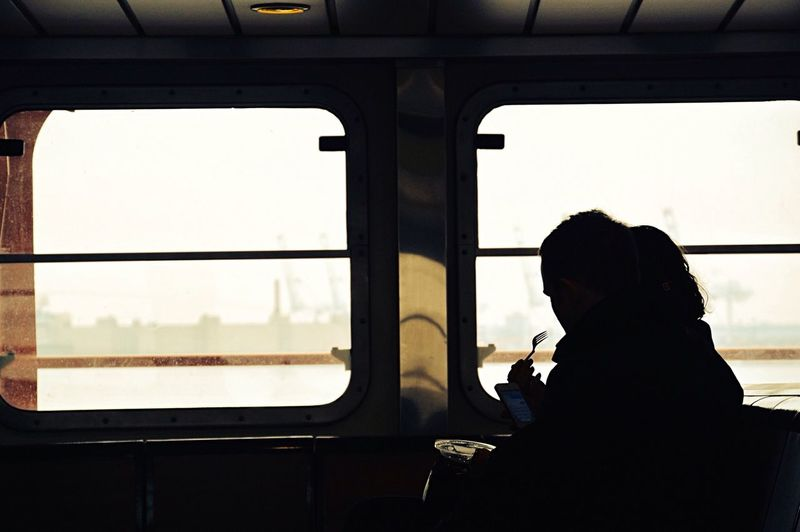 Silhouette man sitting inside staten island ferry and working on mobile phone
