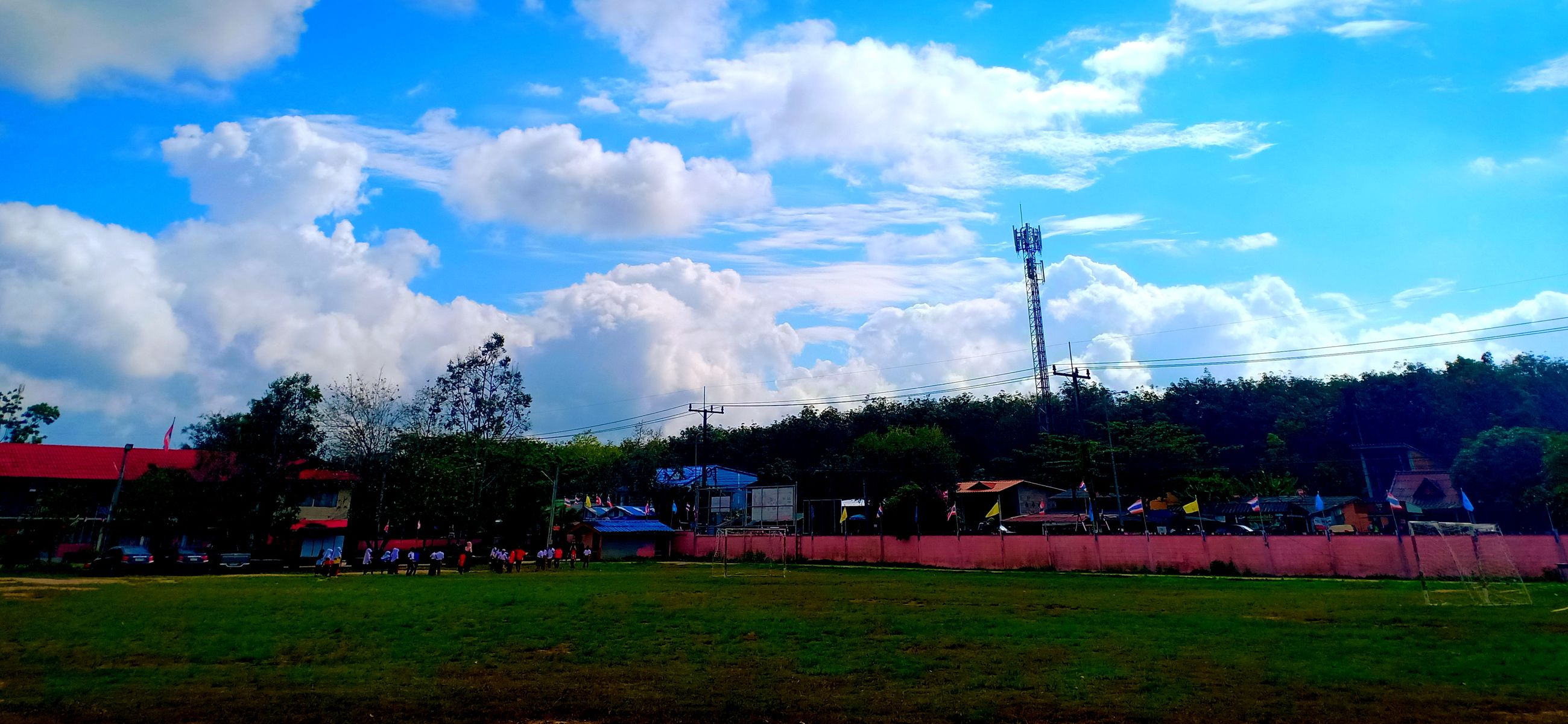 cloud - sky, sky, plant, grass, architecture, building exterior, tree, built structure, nature, land, field, day, landscape, environment, outdoors, incidental people, group of people, sport, green color, building