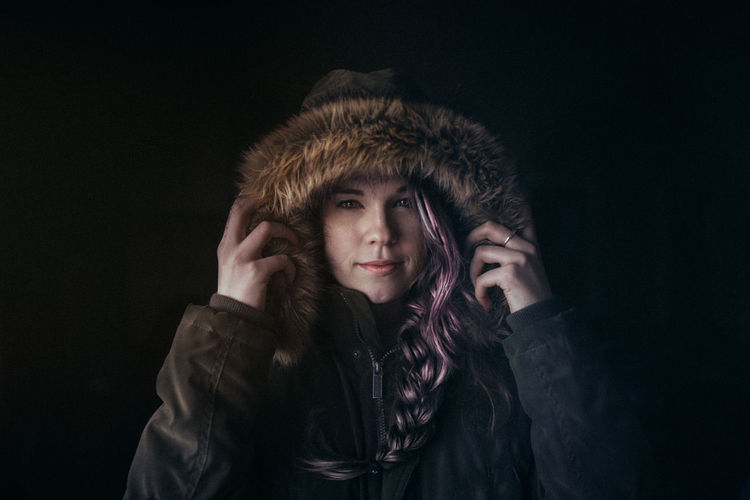 Portrait of woman wearing fur hood against black background