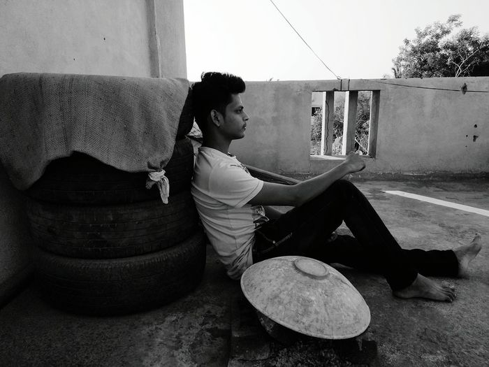 Side view full length of young man sitting on terrace