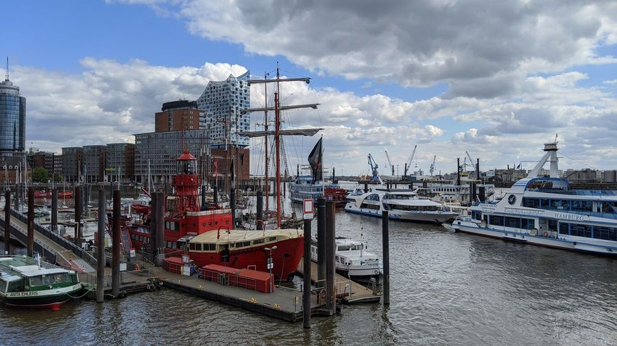 Sailboats moored at harbor against sky in city