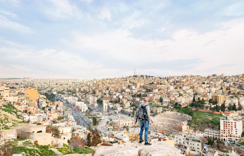 Rear view of man standing on cliff in city