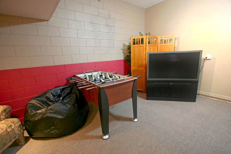 A Games Room with Foosball Table and TV Architecture Bean Bag Built Structure Chair Domestic Room Flooring Foosball Foosball Table Furniture Games Room Home Interior Indoors  No People Pillow Seat Still Life Table Television Set Tv Wall Wall - Building Feature