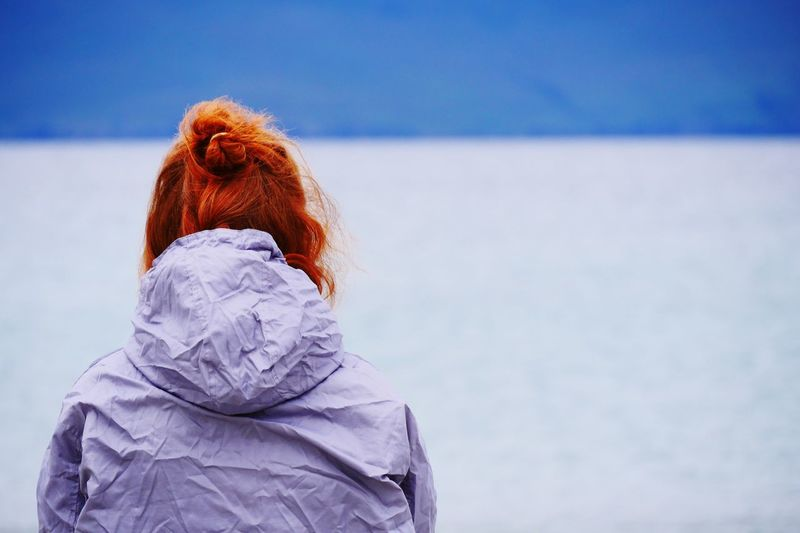 Rear view of woman in warm clothing against sky during winter