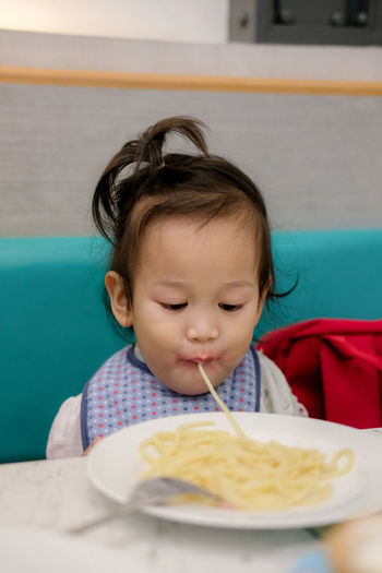 Cute girl eating spaghetti while sitting in restaurant