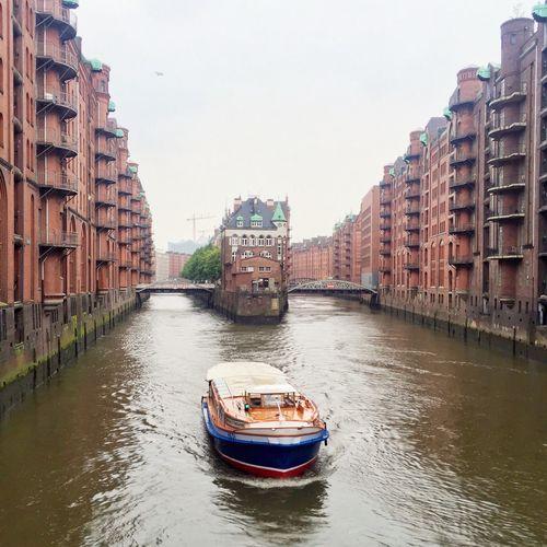 Passenger Craft On Elbe River Amidst Warehouses At Speicherstadt