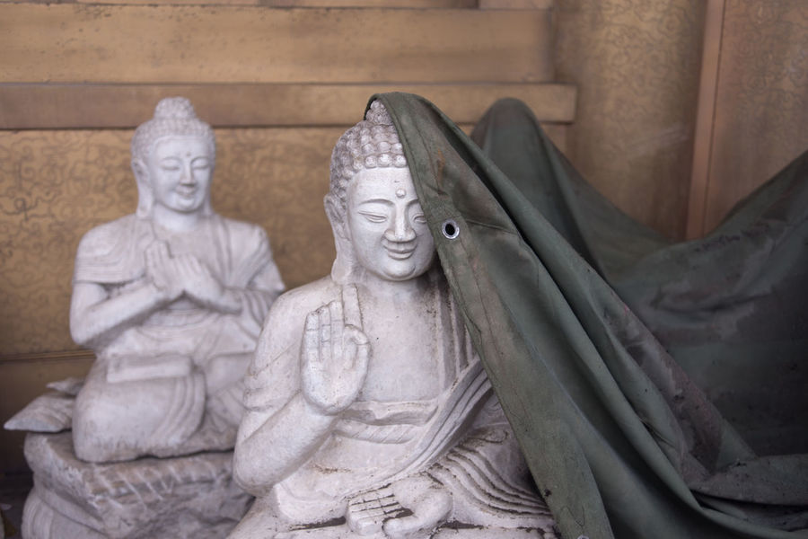 A statue of smiling Buddha with part of the face covered by rain cloth. Buddha Fun God Happy Palm Sitting Abstract Covered Face Gesturing Hand Mona Lisa Mysterious Rain Clothes Rain Cover Sculpture Shy Smiling Statue