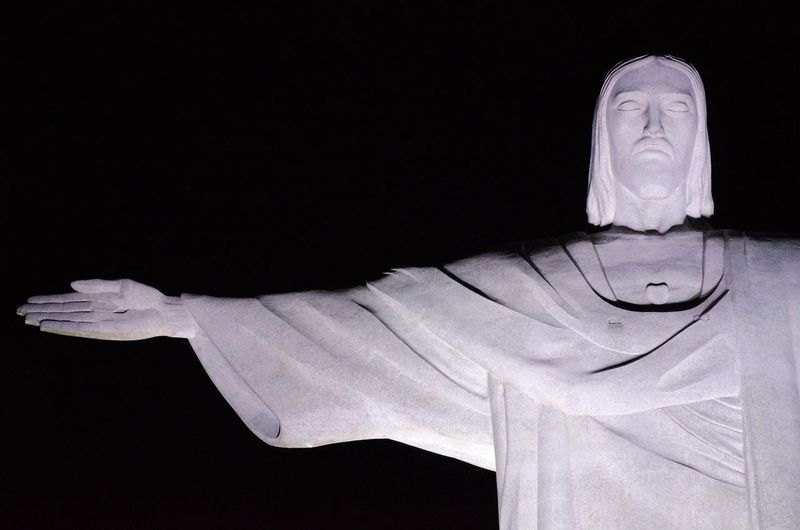 Close-up of jesus christ statue against black background
