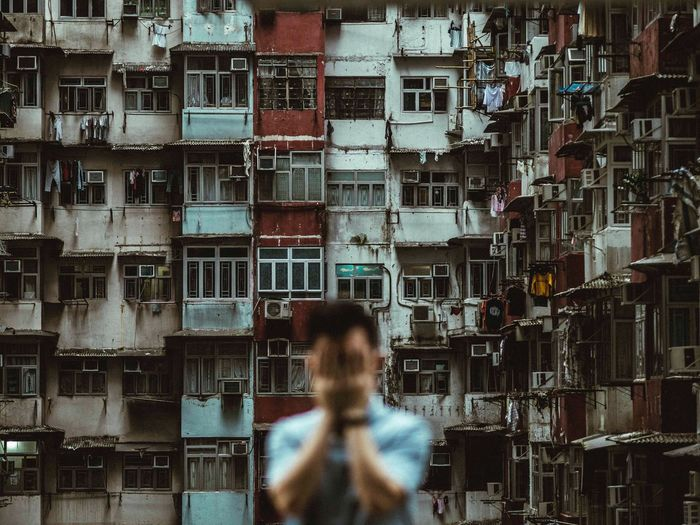 Blurred image of man covering his face standing against residential buildings in city